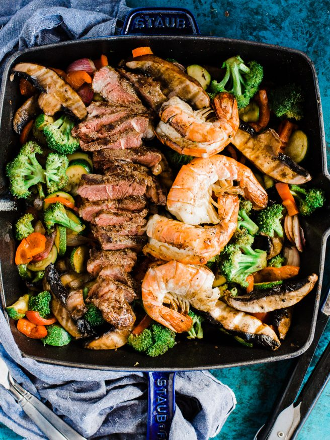 A Surf n' Turf Paleo bowl with Steak and Shrimp, over bell peppers, shallots, portabella mushroom, zucchini with a savory seasoning.