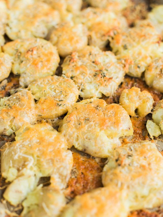 Smashed Potatoes smothered in a herb garlic butter with parmesan and cheddar cheese. Perfect comfort food side and is the best smashed potato recipe ever!