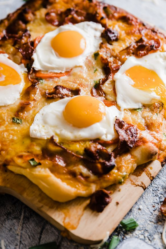 A delicious breakfast pizza loaded with bacon sausage, onion and red bell pepper, then topped with sunny side up eggs. Great weekend breakfast or a breakfast for dinner meal!