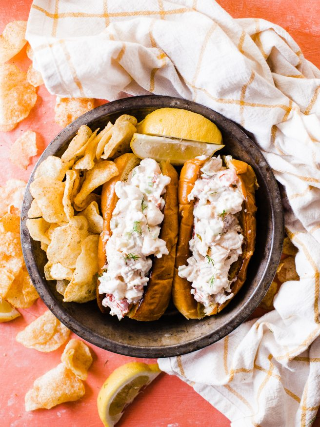 Smoked lobster roll with old bay seasoned chips is the best way to enjoy the summer! Smoked  lobster on a traeger grill and loaded on toasted brioche buns.