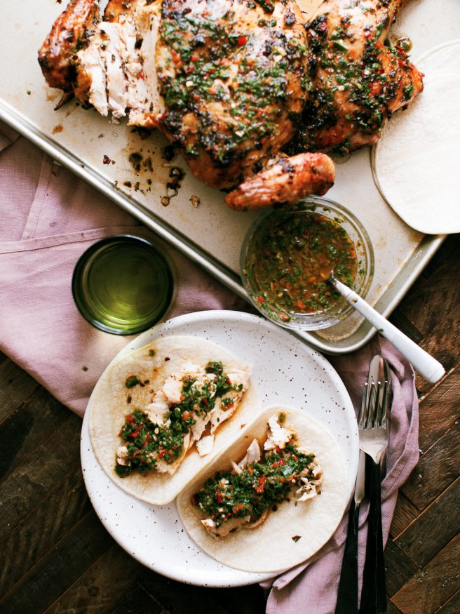 Chimichurri spatchcock chicken cooked on a wood fire grill. Tons of bold, zesty flavors and is a great weekend dinner idea