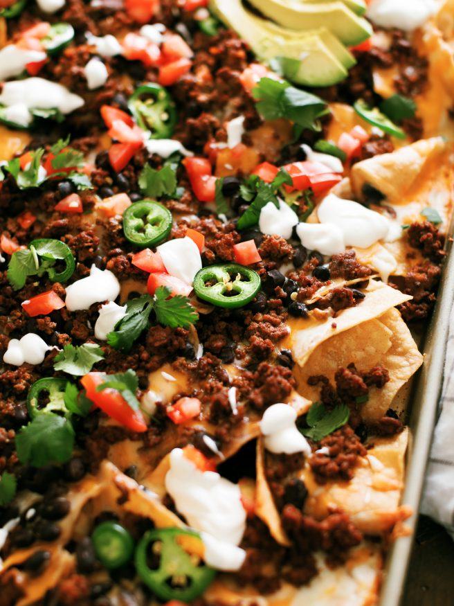 Taco Night Sheet Pan Nachos are a great way to put a spin on taco night. Taco seasoned ground beef and all your favorite taco toppings on sheet pan nachos.