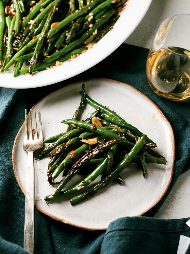 These blistered green beans are fried lightly in oil until blistered, then tossed in a spicy Asian cuisine inspired sauce that is out of this world!