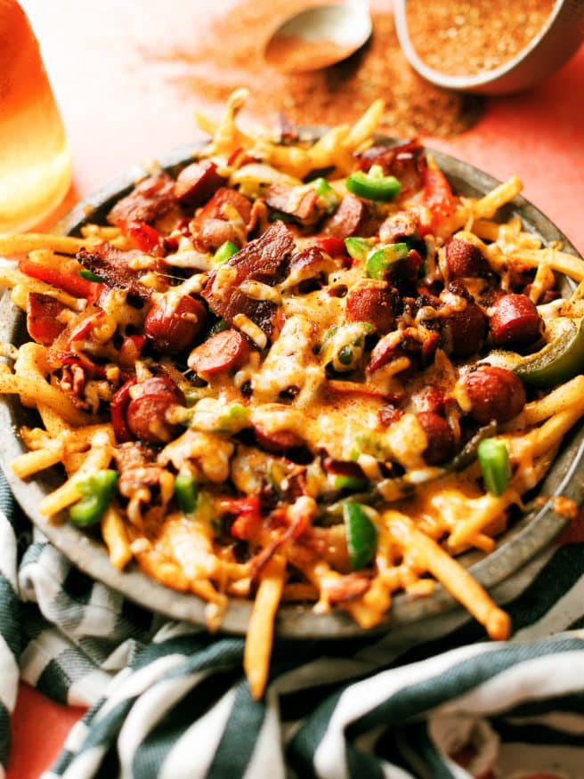 LA Street Meat Cheese fries are topped with cheese, hot dog, peppers and onion, and a spicy fry seasoning that is out of this world. You need to try this!