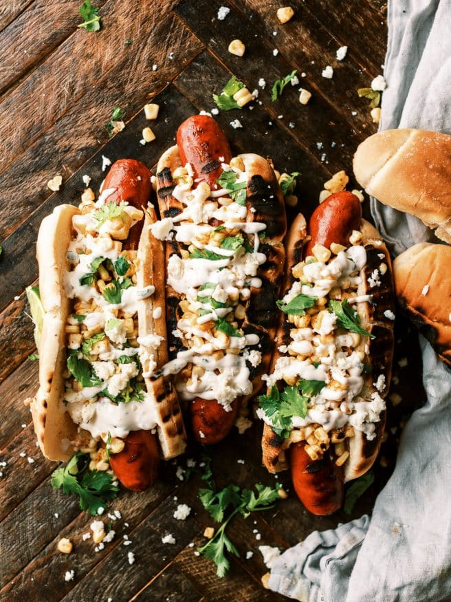 Grilled Andouille sausage hot dog, topped with grilled corn with a little elote seasoning, and a cilantro aioli. It's an explosion of flavors in one bite.