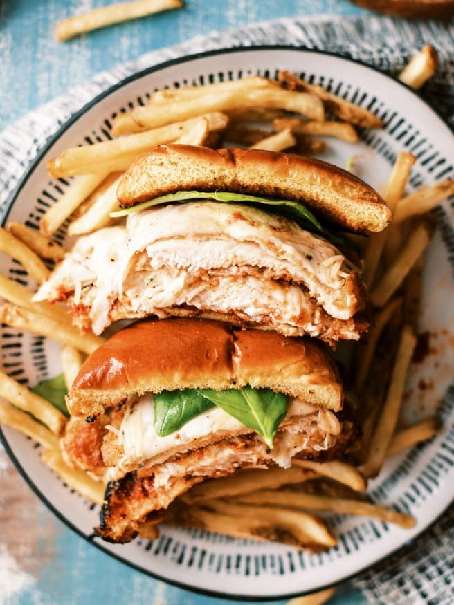 Chicken Parmesan Sandwiches in the theme of a burger. They're a delicious way to change up your chicken Parmesan and so fun to eat!