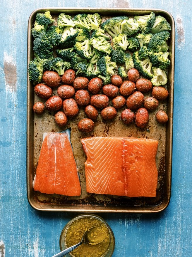 Easy weeknight Sheet Pan recipe with salmon glazed with a lemony honey butter garlic sauce served with baby red potatoes and broccoli. It's easy and a well rounded meal!
