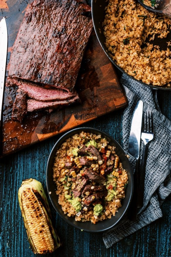 Cilantro Lime Cauliflower rice topped with fresh guacamole, and perfectly seasoned flank steak for a great low carb lunch or dinner!