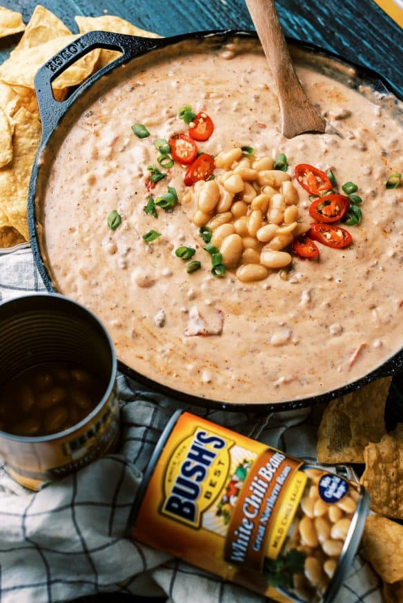 This white bean queso dip is loaded with all sorts of goodness.White Chili Beans , ground beef and all sorts of cheese. It's got tailgating vibes all over it!