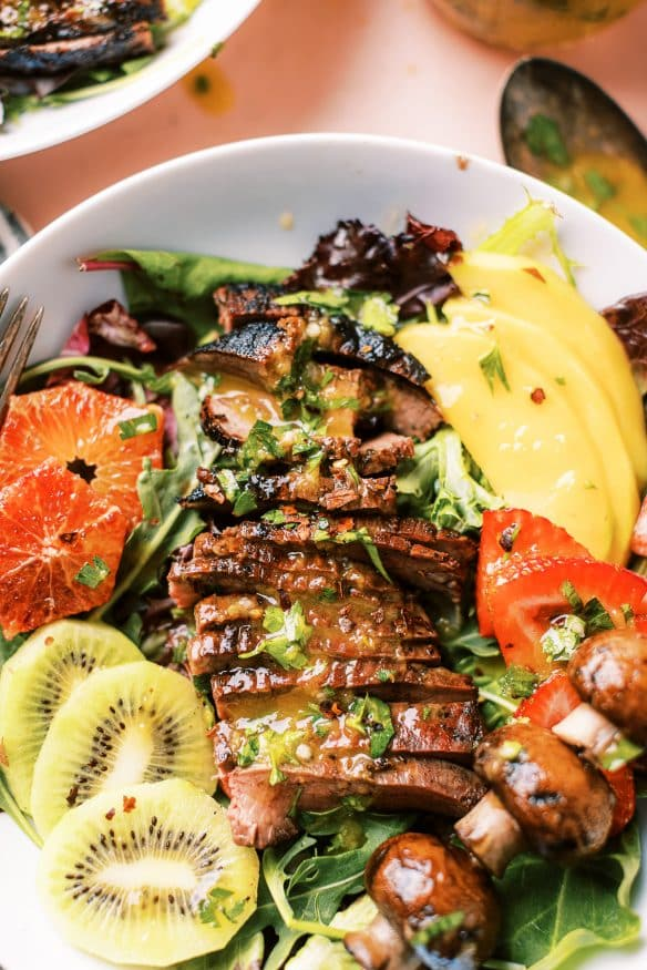This grilled flank steak summer salad with mango vinaigrette topped with fresh summer fruit for a little sweet, savory and tangy flavors.