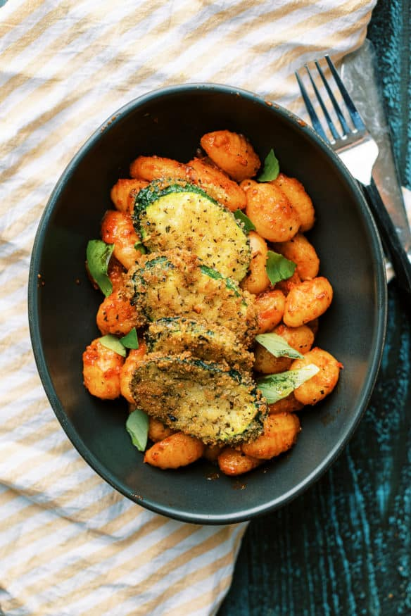 Panko breaded fried zucchini is a great way to inject some veggies into pasta night. Italian seasoned and lightly fried then topped on some gnocchi is perfect!