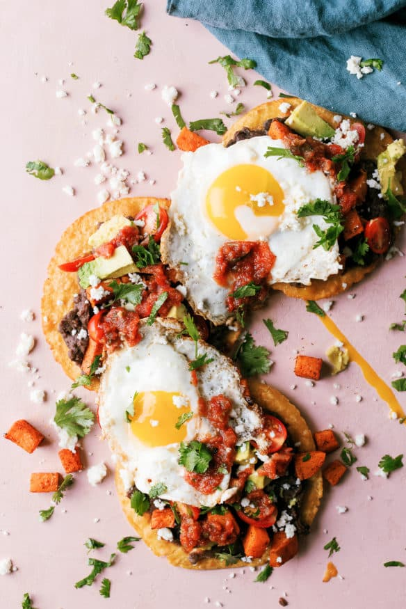 Huevos Rancheros Tostadas with some seasoned sweet potatoes on top makes the perfect breakfast, or breakfast for dinner recipe!