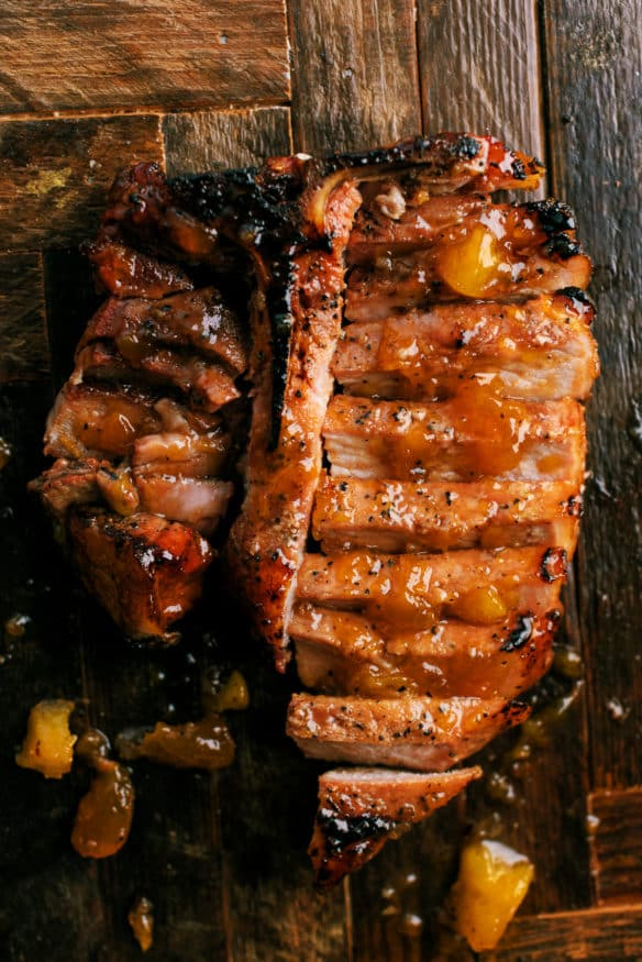 low and slow smoked pork chops topped with a peach glaze that is out of this cooked down with a little bourbon that makes a killer dinner!